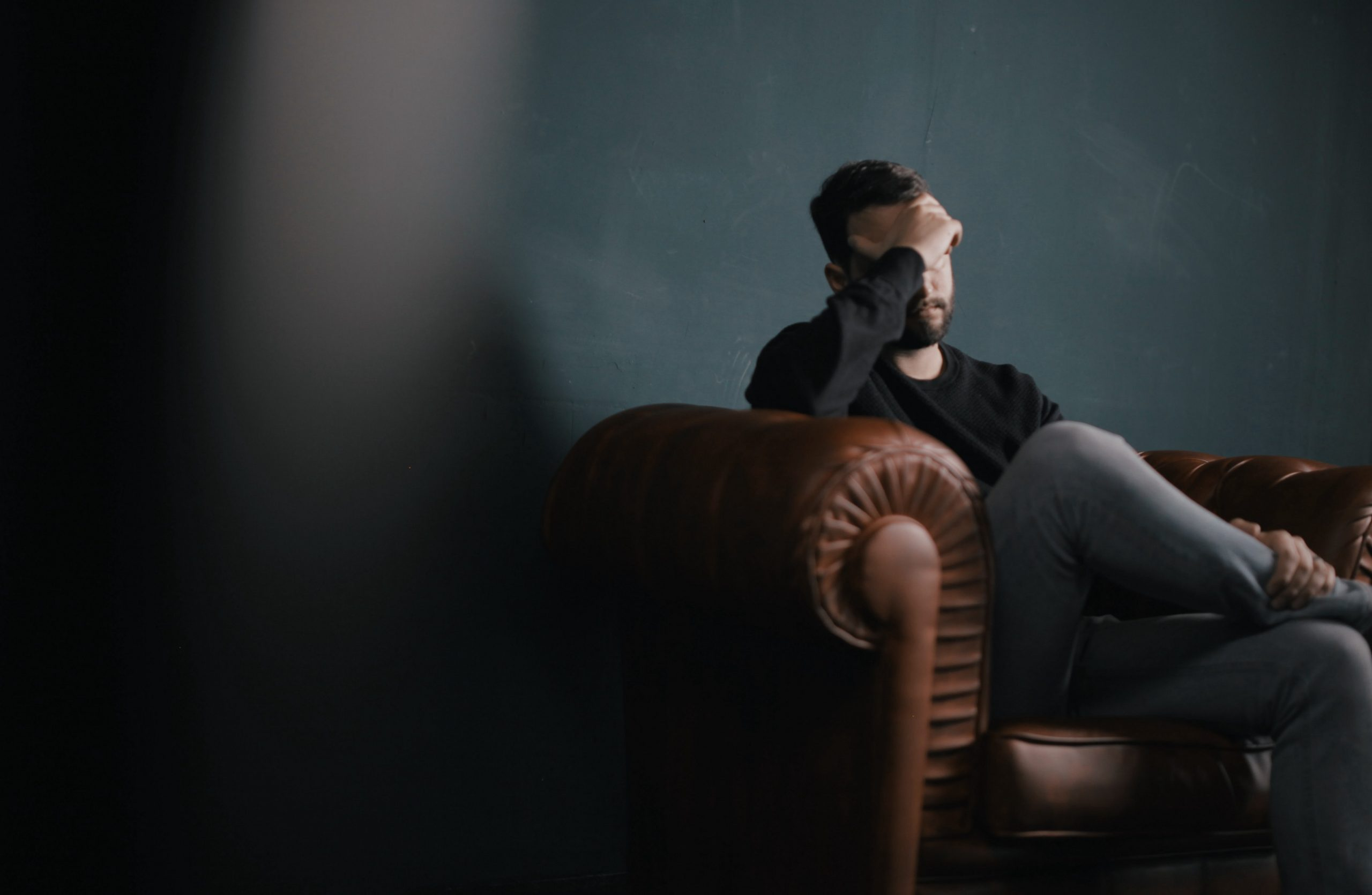 Person sitting on sofa looking stressed